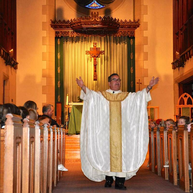 Fr. Wayne Watts delivering a sermon in the aisle at St. Joseph Church